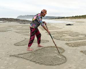 Dunedin artist Tony Gillies and Bex Willis add the final touches to the 1.7km sand mural at St...