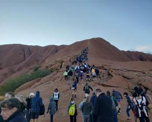 Tourists crowd a trail as they climb Uluru recently. Photo: Reuters