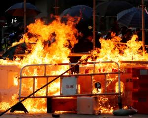 Protesters set fire at a barricade as policemen advance during an anti-government protest in Hong...