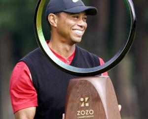 Tiger Woods celebrates with the trophy after winning the Zozo Championship. Photo: Kyodo/via...