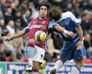 Aston Villa's Juan Pablo Angel is challenged by Wigan Athletic's Arjan De Zeeuw for the ball in...