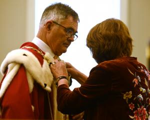 Dave Cull's wife, Joan Wilson, adjusts his robes. Photo: Linda Robertson