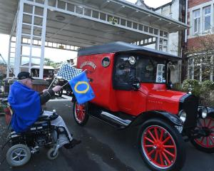 Ross Home resident Trevor Rodger (80) waves away vintage vehicles with his starting flags...