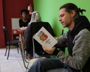 Inspired by 'More of Us': Charles Olsen reads in a Senegalese restaurant in Madrid.