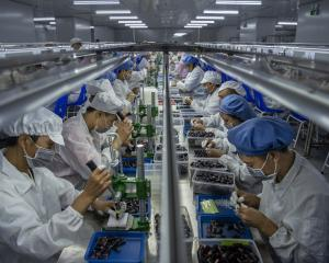 Workers make pods for e-cigarettes on the production line at Kanger Tech, one of China's leading...