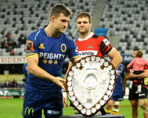 Otago captain Michael Collins presents his Canterbury counterpart, Luke Whitelock, with the...