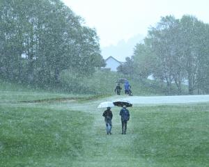 Golfers competing in the Otago championships seek shelter during a hailstorm at the seventh hole...