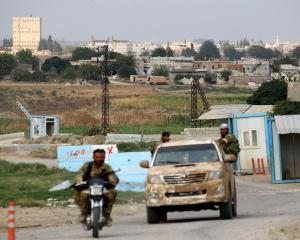 Buildings and houses are seen as Turkey-backed Syrian rebel fighters patrol near Ras al Ain Town,...