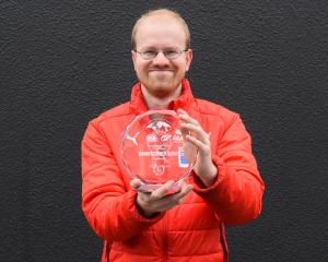 Dunedin electronic sports champion Simon Bishop (29) with a trophy he won racing digital cars in...