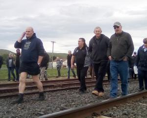 Affected family members and friends walk along the Main South Line at Waipahi Station, as part of...