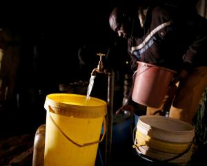 A resident collects water at night from an electric-powered borehole in Harare, as Zimbabwe faces...