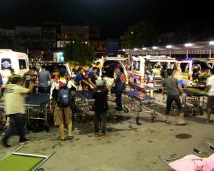 Rescue workers transfer the bodies of victims at a hospital in Yala province, southern Thailand....
