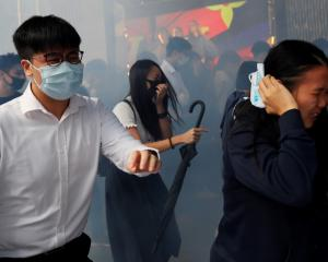 People run away from tear gas as they attend a flash mob anti-government protest at the financial...