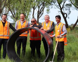 From left, with a section of pipe similar to that to be put underground, are Gareth McGrath and...