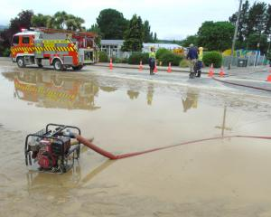 The Roxburgh Volunteer Fire Brigade helps to pump water off Roxburgh's main street after the...