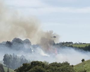 A helicopter with a monsoon bucket fights the fire on Scroggs Hill as seen from Kayforce St,...