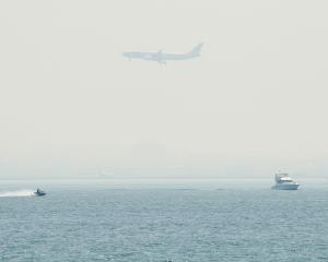 A plane flies over smoke-covered Botany Bay as it comes in to land at Sydney airport, while fires...