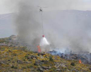 A helicopter discharges a monsoon bucket over the scrub fire. PHOTO: ADAM BURNS