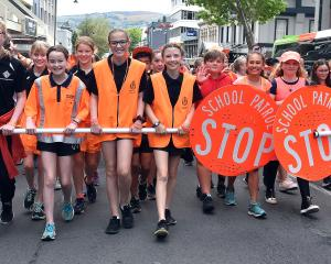 School traffic patrol team members are all smiles as they parade along George St dressed in...