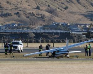 Police and Queenstown airport fire rescue staff examine the Cessna 177 damaged in an emergency...