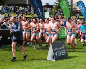 Wakatipu Rugby Club players cross the line at the Queenstown International Marathon on Saturday....