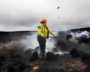 Turning over smouldering ground to prevent the fire from reigniting at the Te Papanui...