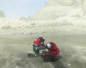 The crew of the Westpac Rescue Helicopter shelters from the dust kicked up by their chopper...
