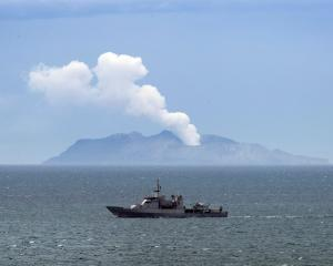 Naval vessel HMNZS Wellington passes White island yesterday as it helps in the recovery mission...