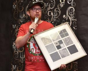 Teacher and musician Brendan Christie accepts an artwork by Dunedin visual artist Lynn Taylor, to...