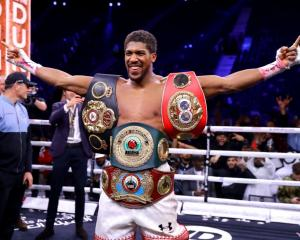 Anthony Joshua celebrates after regaining four of the world heavyweight championship belts...