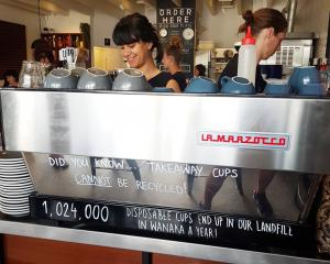 Jorden Lahood makes coffee at Big Fig, where staff use the coffee machine as a billboard to...