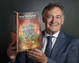 SBS chairman, John Ward, shows off the book celebrating the bank's 150th year. PHOTO: PETER...