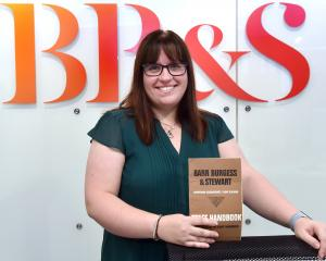 Barr Burgess and Stewart managing director Christine McNamara holds an old staff handbook. Photo:...