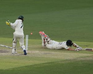 Colin de Grandhomme of New Zealand dives to avoid a run-out by Tim Paine of Australia. Photo:...