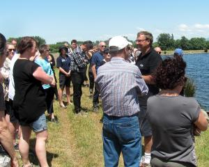 Chris Allen addresses teachers alongside the 150,000cu m water storage pond on his farm at...