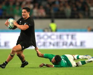 All Black midfield back Anton Lienert-Brown tries to get away from Irish replacement back Joey...