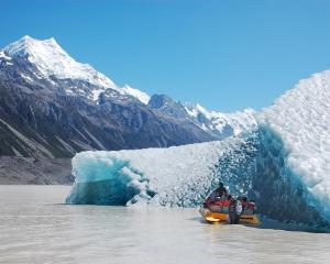 A Magic Memories image of tourists beside an iceberg, with Mt Cook in the distance. Photo: Magic...