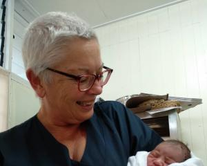 Invercargill nurse Anne Dymond holds baby Annegelo — a baby she delivered while at Leulemoega...