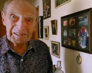 Cromwell man Tom Landreth admires some of the photos hanging in his lounge. Mr Landreth will...
