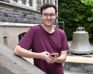 Former Dunedin student Benjamin Riordan with the University of Otago bell which is rung after...