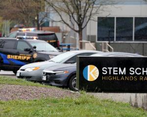 Police vehicles are stationed outside the school following the shooting at the Science,...