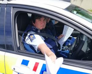 Constable Ruth Parsons hands trespass notices to environmental activist Sam Murphy in Dunedin...