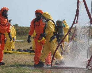 Recovery teams go through the decontamination process after returning from Whakaari/ White Island...