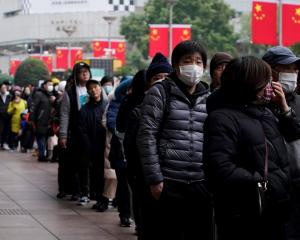 People queue to buy masks at a pharmacy in China. Photo: Reuters