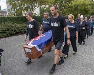 Camilla and Julian Cox and members of action group Patient Voice Aotearoa carry a coffin towards...