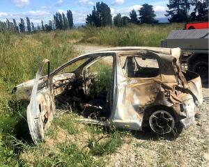 Burnt-out cars like this one being dumped along the Waimakariri River could be a fire risk.