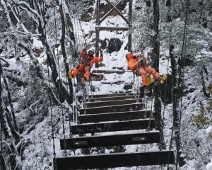 Abseil Access crew members brave winter snow to work on a suspension bridge on the Paparoa Track....