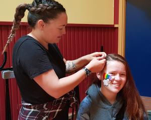 The Mack volunteer hairdresser Justine Beer-Williams braids the hair of Milton Free Day attendee...