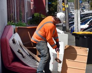 A contractor breaks up discarded furniture before removing it on Dundas St, in Dunedin's student...