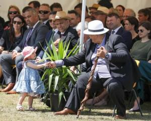 Prime Minister Jacinda Ardern's daughter Neve Te Aroha Gayford plays at the feet of those sitting...